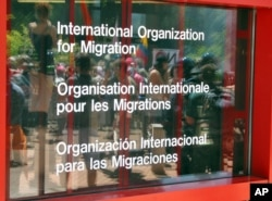 FILE - Protesters are seen reflected in the door to the office of the International Organization for Migration in Geneva, May 30, 2003.