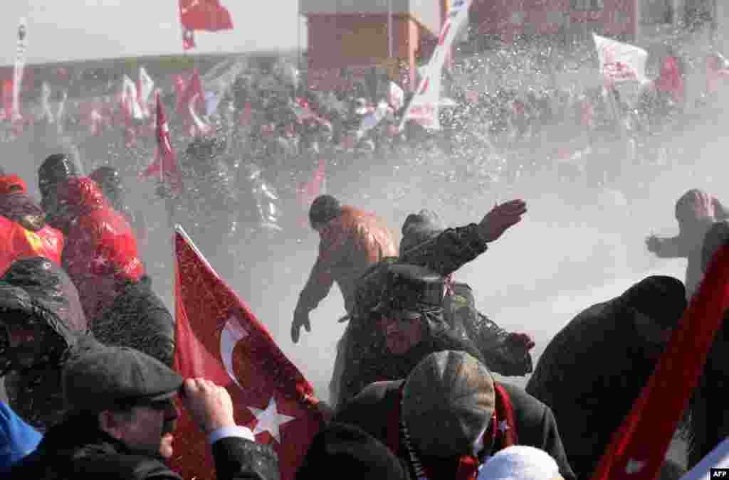 Pasukan keamanan Turki menyemprotkan air dan menembakkan gas air mata ke arah para demonstran yang berusaha memasuki gedung pengadilan di Silivri dekat Istanbul, Turki.