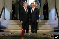 France's President Francois Hollande stands with German President Joachim Gauck in the crypt of the the National Monument of Hartmannswillerkop, in Wattwiller, eastern France, Aug. 3, 2014.