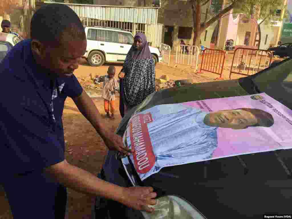 Un supporter du président sortant pose une de ses affiches sur son véhicule, Niamey, 15 mardi 2016. (VOA/Bagassi Koura)