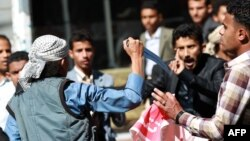 A Shi'ite Houthi rebel threatens Yemeni protesters during a rally against the control of the capital by Houthi rebels, Jan. 24, 2015.