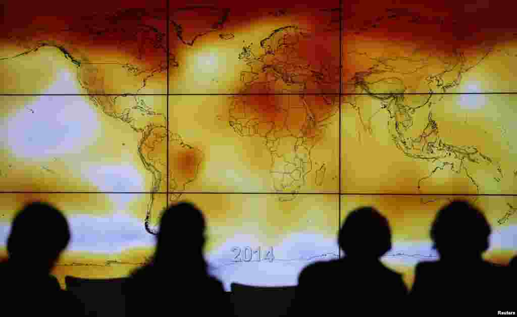 Participants are seen in silhouette as they look at a screen showing a world map with climate anomalies during the World Climate Change Conference 2015 (COP21) at Le Bourget, near Paris, France.