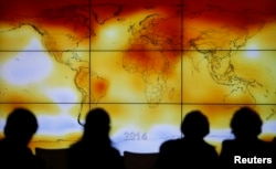 Participants are seen in silhouette as they look at a screen showing a world map with climate anomalies during the World Climate Change Conference 2015 (COP21) at Le Bourget, near Paris, France, December 8, 2015.