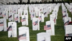 U.S. flags are seen at grave sites at Arlington National Cemetery in Arlington, Virginia, May 24, 2019, ahead of Memorial Day weekend.