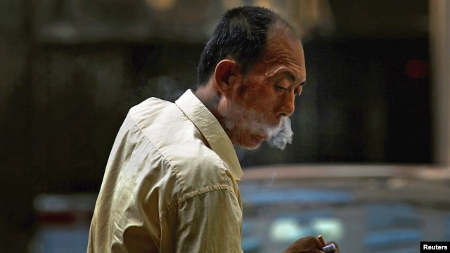 A taxi driver takes a cigarette break in central Beijing, China, May 28, 2012.