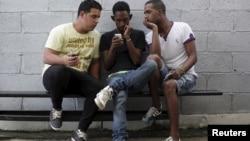 Jóvenes usan el internet por medio de servicio wifi gratis cerca de un estudio de arte en La Habana.
