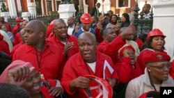 Julius Malema, center, leader of the Economic Freedom Fighters (EFF) party stands outside Parliament after he and party members heckled South African President Jacob Zuma, Cape Town, South Africa, Aug. 21, 2014.