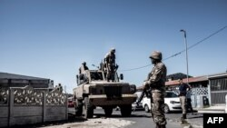 South African National Defense Force (SANDF) soldiers stand next to an Armored Personnel Carrier in the Cape Flats area of Cape Town, on March 30, 2020, during a patrol to enforce a nationwide lockdown.