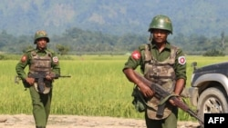 In this photograph taken on October 21, 2016, armed Myanmar army soldiers patrol a village in Maungdaw located in Rakhine State as security operation continue following the October 9, 2016 attacks by armed militant Muslim. - The United Nations called for