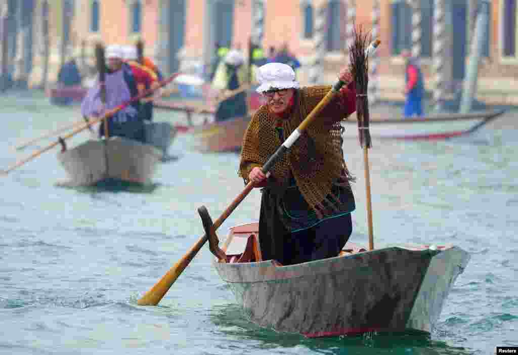 បុរសម្នាក់តុបតែងជាតួអង្គ La Befana តួអង្គស្ត្រីចំណាស់ម្នាក់ដែលគេជឿថា ជាអ្នកនាំកាដូឲ្យក្មេងៗក្នុងពិធីបុណ្យ Epiphany ចែវទូកនៅក្នុងប្រឡាយ Grand Canal នៅក្នុងក្រុង Venice ប្រទេសអ៊ីតាលី កាលពីថ្ងៃទី៦ ខែមករា ឆ្នាំ២០១៨។