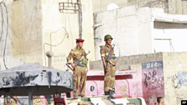 Army soldiers watch as women march during a demonstration to demand the ouster of Yemen's President Ali Abdullah Saleh in the southern city of Taiz Apr 14 2011