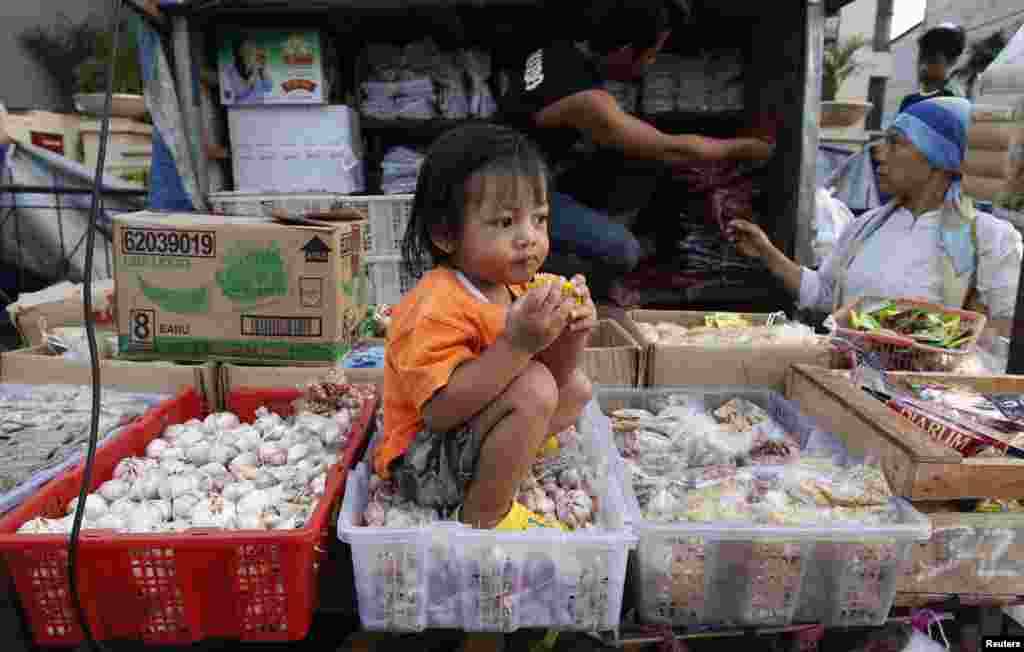 A girl sits in a garlic basket at a street market in Jakarta, Indonesia.