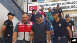 FILE - Turkish police officers escort Turkish pop singer Atilla Tas, center, to police headquarters following his arrest, in Istanbul, Turkey, Sept. 3, 2016.