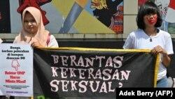 Aktivis perempuan dari gerakan anti kekerasan memegang spanduk bertuliskan
