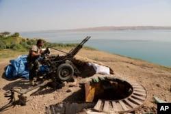 Курдски борец го подготвува оружјето на позиција близу браната во Мосул