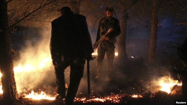 Members of the Free Syrian Army set up a fire to obscure the Kurdish militants' vision, while standing alert during a truce on  top of a hilly mountain in the Kurdish area of al-Qaftal, overlooking the town of Azaz, October 31, 2012.