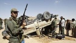 یک سرباز تونسی در کنار خودروی متعلق به نیروهای وفادار به معمر قذافی که واژگون شده است در نزدیکی مرز تونس با لیبی - ۲۹ آوریل ۲۰۱۱