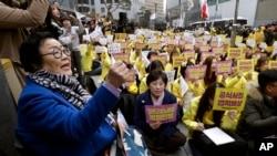 """In this March 1, 2017, file photo, former """"comfort woman"""" Lee Yong-soo, left, who was forced to serve for the Japanese troops as a sex slave during World War II, shouts slogans during a rally to mark the March First Independence Movement Day. (AP Photo/Ahn Young-joon, File)"""