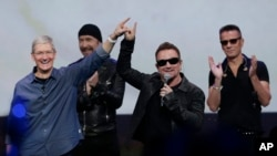 Apple CEO Tim Cook, left, with U2 members, The Edge, Bono, and Larry Mullen Jr. announce new products on Sept. 9, 2014, in Cupertino, Calif. (AP Photo/Marcio Jose Sanchez)