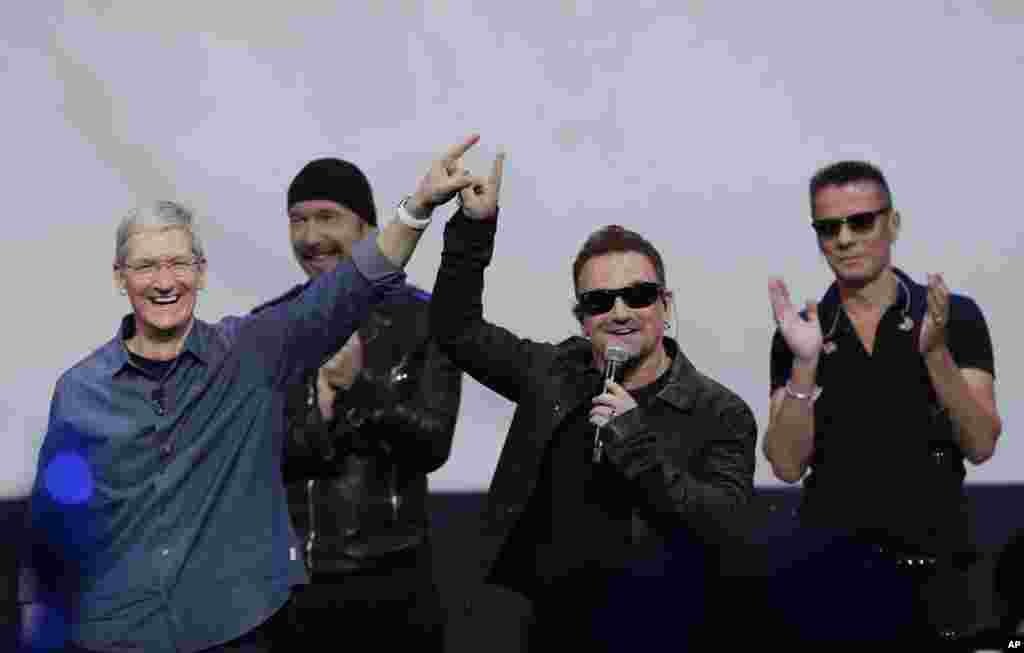 Apple CEO Tim Cook (left) smiles next to U2 members, The Edge, Bono, and Larry Mullen Jr. during an announcement of new products, in Cupertino, California, Sept. 9, 2014.