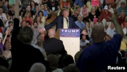 Audience members raise their hands to ask U.S. Republican presidential candidate Donald Trump a question at a campaign town hall meeting in Rochester, New Hampshire September 17, 2015.