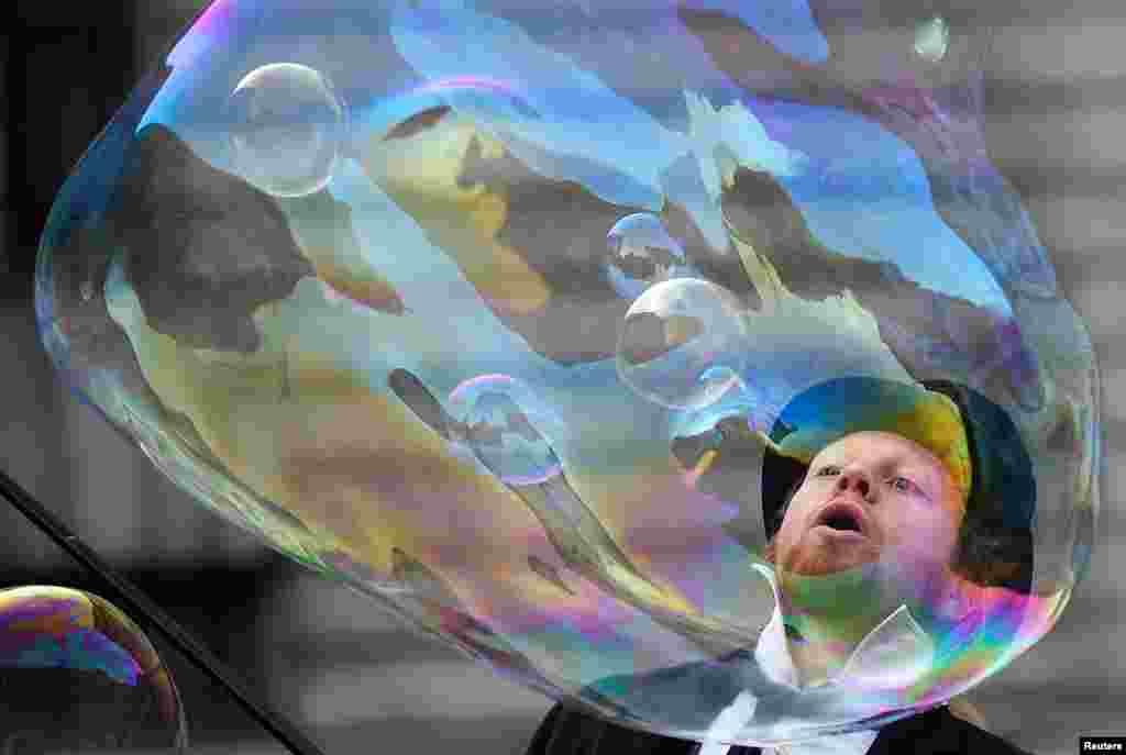ایجاد یک حباب رنگی بزرگ توسط یک هنرمند خیابانی مقابل ساختمان موزه تاریخ طبیعی لندن