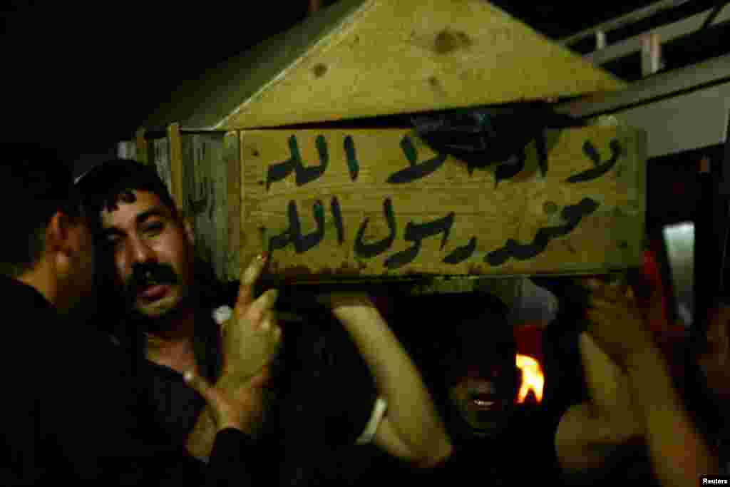 Men carry the coffin of a victim killed in one of April 15's bomb attacks, during a funeral in Najaf, Iraq.
