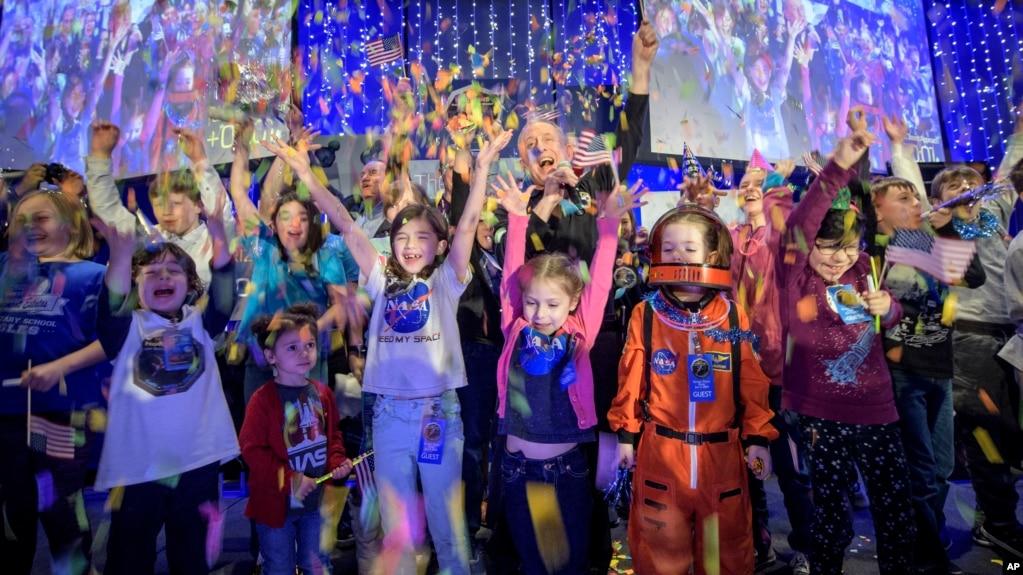 En esta foto proporcionada por la NASA, el principal científico del New Horizons, Alan Stern, del Southwest Research Institute en Boulder, Colorado, celebra con niños de colegio el momento exacto en el que la nave hizo su acercamiento más cercano al objeto del cinturón de Kuipe.