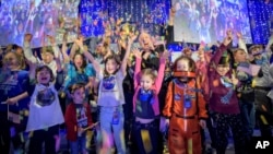 In this photo provided by NASA, a NASA scientist celebrates with school children at the exact moment that the New Horizons spacecraft made the closest approach of Kuiper Belt object Ultima Thule, Jan. 1, 2019, in Laurel, Md.