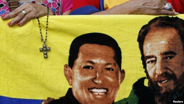 Một người ủng hộ Tổng thống Chavez cầm chiếc Thánh giá cạnh bức ảnh của ông và nhà cựu lãnh đạo Cuba, Fidel Castro (phải), 5/1/13