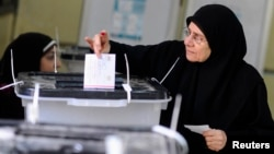 A woman casts her vote at a polling center during a referendum on Egypt's new constitution in Cairo, Jan. 14, 2014.