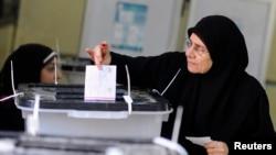 Seorang wanita memasukkan surat suaranya ke dalam kotak di sebuah TPS di Kairo, dalam pemungutan suara untuk mereferendum UUD baru Mesir (14/1).