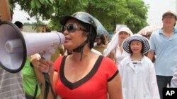 ນາງ Bui Thi Minh Hang (ເສື້ອແດງ) ທີ່ຖືກຈັບໄປກັກຂັງໃນວັນທີ 27 ພະຈິກທີ່ຜ່ານມາ ລຸນຫລັງໄດ້ເຂົ້າຮ່ວມໃນການປະທ້ວງນ້ອຍໆ ຄັ້ງນຶ່ງຢູ່ໃນນະຄອນໂຮ່ຈິມິນ ຢູ່ພາກໃຕ້ຂອງຫວຽດນາມ.