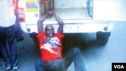 Emidio Macie sendo arrastado por um carro da polícia sul-africana.