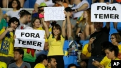 """Fans hold signs that read in Portuguese """"Out with Temer"""" prior to a women's Olympic football tournament match between Brazil and Sweden at the Olympic Stadium in Rio de Janeiro, Brazil, Aug. 6, 2016."""
