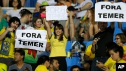 "fans hold signs that read in Portuguese; ""Temer Out"" prior to a group E match of the women's Olympic football tournament between Brazil and Sweden at the Rio Olympic Stadium in Rio de Janeiro, Brazil, Aug. 6, 2016."