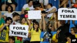 """Des fans tiennent des pancartes sur lesquels on peut lire """"Temer Dehors"""" juste avant un match entre le Brésil et la Suède aux JO de Rio, Brésil, le 6 août 2016."""