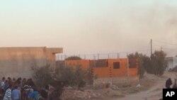 Warga setempat berlindung dari tembakan ketika pasukan keamanan Tunisia menyerbu sebuah rumah di El Aouija, pinggiran kota Ben Guerdane, dekat perbatasan Libya , Rabu (2/3).