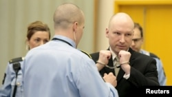 Anders Breivik, serving a sentence for the 2011 killing of 77 people, has his handcuffs removed inside the court room in Skien prison, Norway, March 16, 2016. He claims that conditions to which he is subjected in prison are a violation of his human rights.