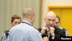 Petugas melepaskan borgol dari tangan terpidana pembunuhan masal Anders Behring Breivik dalam ruang pengadilan di penjara Skien, Norwegia (16/3).