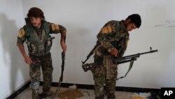 یک جنگجوی عرب (چپ) و یک مبارز کرد عضو ائتلاف موسوم به «نیروهای دموکراتیک سوریه» در حال آماده شدن برای نبرد با داعش در رقه - آرشیو