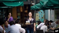 A woman orders cups of coffee at a Starbucks cafe in Beijing, China. (June 2011.)