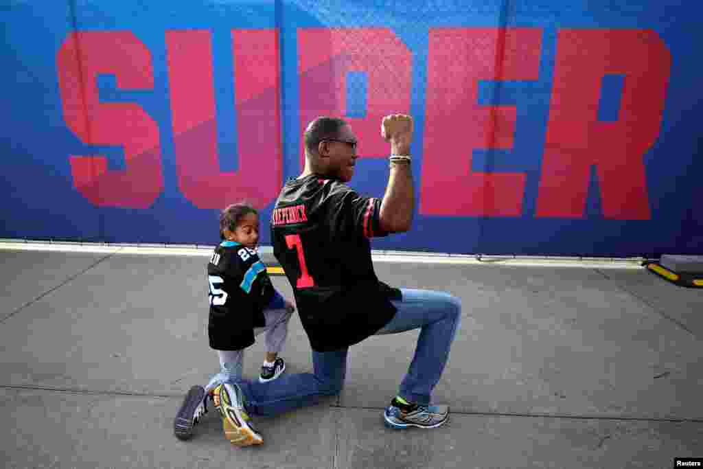 Anar Kahn from Atlanta, kneels with his son while wearing a Colin Kaepernick football jersey outside Mercedes Benz Stadium ahead of Super Bowl LIII in Atlanta, Georgia, Feb. 2, 2019.
