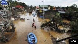 Tim penyelamat menggunakan perahu karet di kawasan banjir di kota Cagayan de Oro, Filipina selatan (17/12).