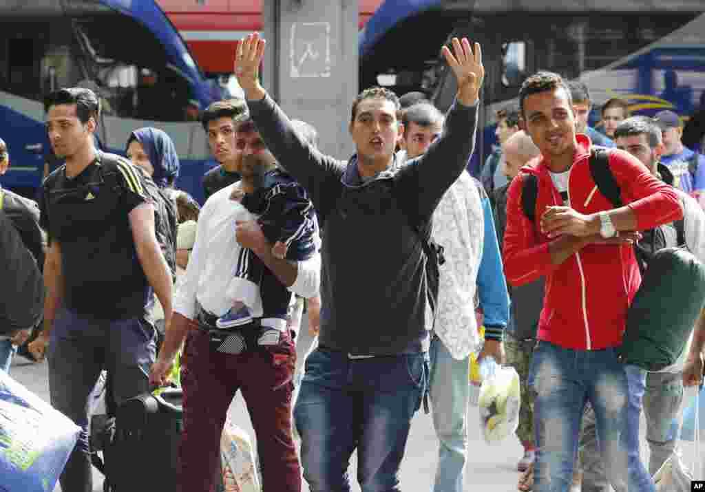 پناهجویانی که روز شنبه وارد ایستگاه قطار مونیخ شدند برای عکاسان دست تکان می دهند.