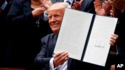 El presidente Donald Trump sostiene una orden ejecutiva firmada para aliviar una regla del IRS que limita la actividad política de las iglesias, el jueves 4 de mayo de 2017, en el Jardín de las Rosas de la Casa Blanca en Washington.
