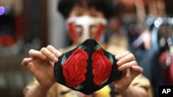 In this Wednesday, April 15, 2020, photo, fashion designer Do Quyen Hoa shows off an embroidery face mask at her studio in Hanoi, Vietnam. The collection of face masks adorned with Vietnamese hand embroideries was created as the world is fighting against