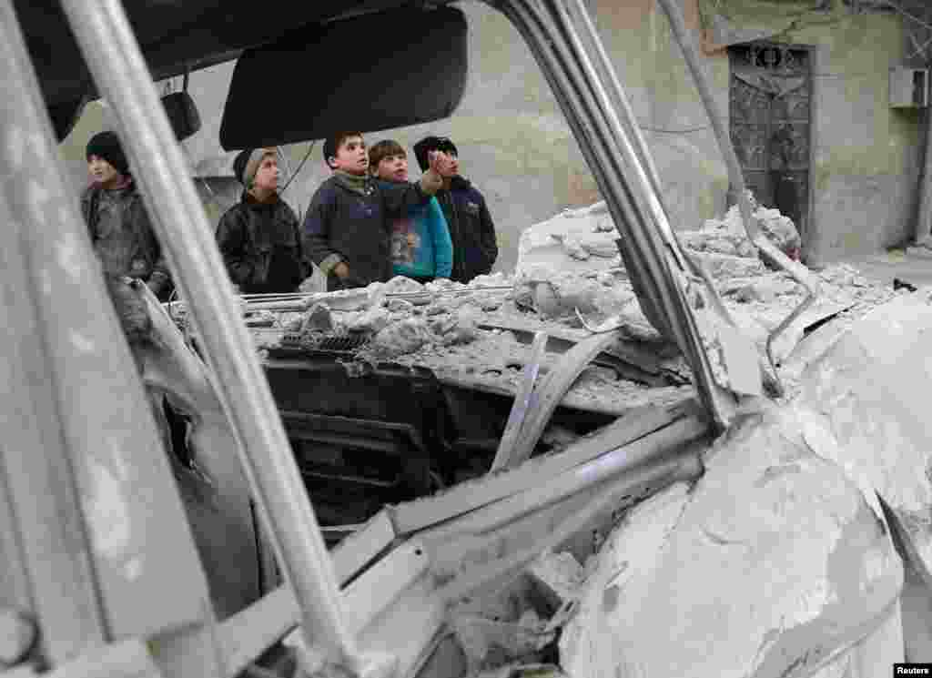 Boys stands near a damaged site after an airstrike on the Eastern Ghouta town of Misraba, Syria.