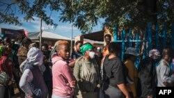Pessoas em fila aguardam a distribuição de comida num parque de estacionamento em Orlando East Communal Hall, Soweto, Joanesburgo, 17 de abril, 2020. (Photo by MARCO LONGARI / AFP)