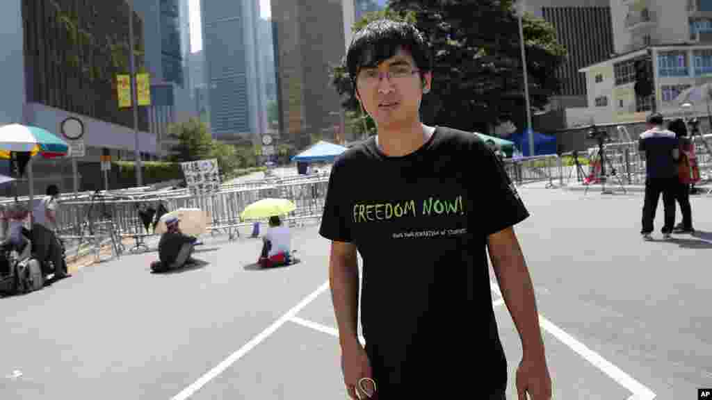 Pro-democracy student leader Alex Chow walks by Hong Kong's Chief Executive Leung Chun-ying's office where a few student protesters are sitting and staging their protest in Hong Kong, Oct. 6, 2014.